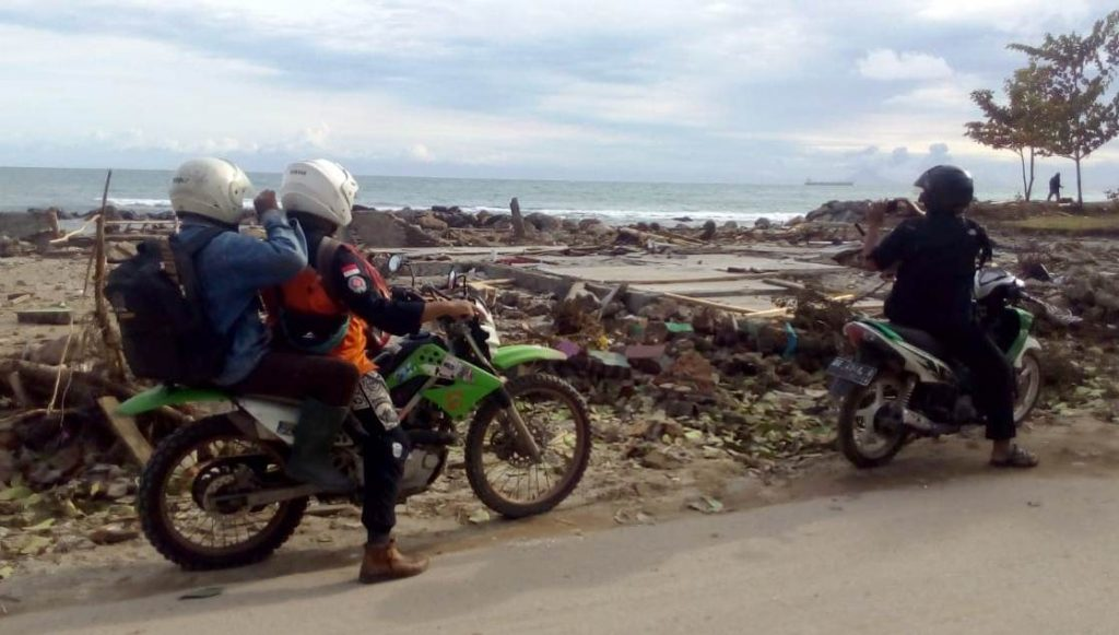 Tim SARMMI di depan rumah Zulfahmi. Tiang, dinding, atap, serta semua perabotan lenyap di sapu tsunami. Yang tersisa hanya lantai dan bak kamar mandi yang tinggal separoh.